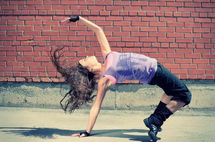 Beautiful teenage girl dancing hip-hop over red brick wall