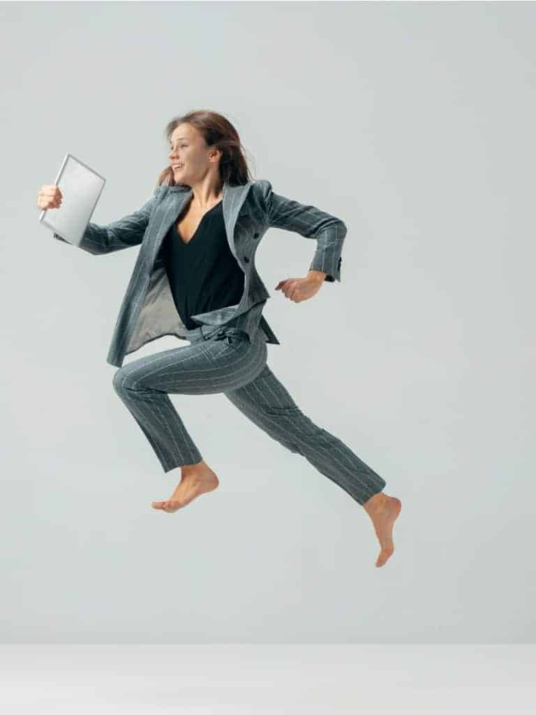 happy-business-woman-dancing-and-smiling-isolated-over-white-picture-id1097380500