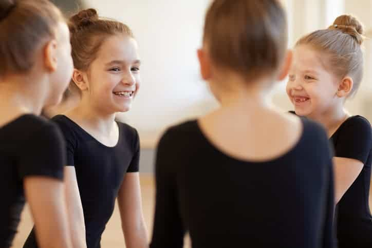 Group of cute girls giggling while sitting in circle during ballet class in studio lit by warm sunlight