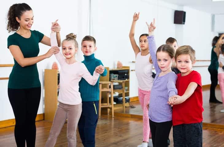 Group of positive person dancing tango in dance studio